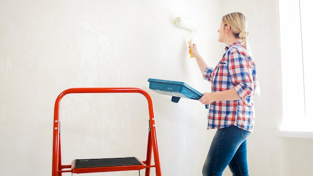 Красивая молодая женщина в клетчатой рубашке делает ремонт дома.