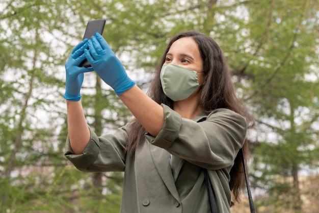 야외 마스크에서 셀카를 복용하는 동안 스마트 폰을 사용하여 천 마스크와 라텍스 장갑에서 아름 다운 젊은 여자