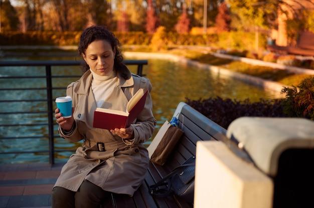 아늑한 따뜻한 트렉 코트를 입은 아름다운 젊은 여성은 물에 반사된 노란색 낙엽이 있는 아름다운 호수 배경에 있는 가을 공원의 나무 벤치에 앉아 책을 읽고 커피를 마신다