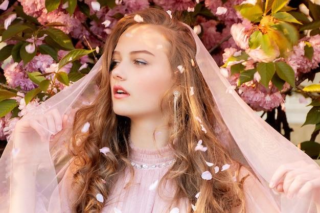 ベールと繊細な桜の花の美しい若い女性