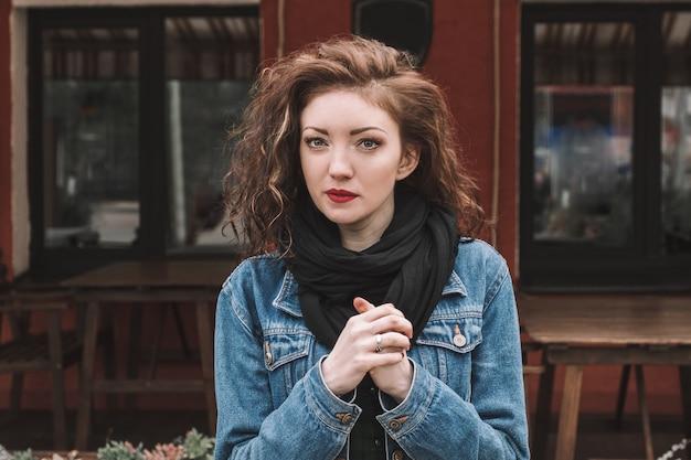 ストリートカフェの近くに立っているデニムジャケットの美しい若い女性