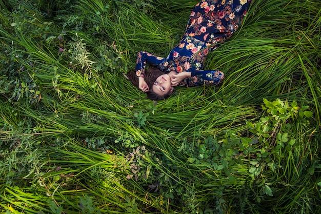 自然の中で草の中に横たわっているドレスの美しい若い女性