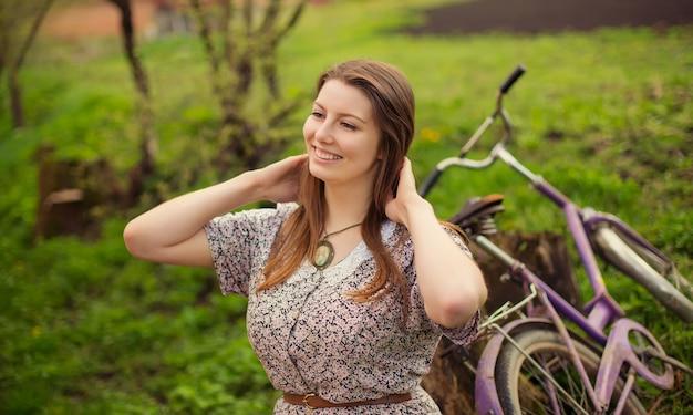 Красивая молодая женщина в платье прогулка со старым винтажным велосипедом