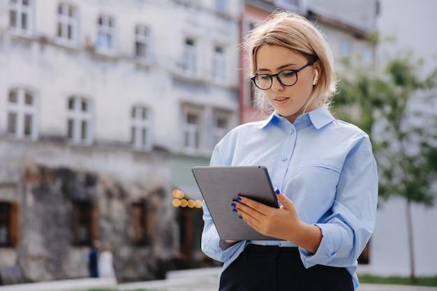 通りに立ってデジタルタブレットを使用して眼鏡とカジュアルウェアの美しい若い女性。都市空間の背景をぼかす。現代の技術コンセプト。