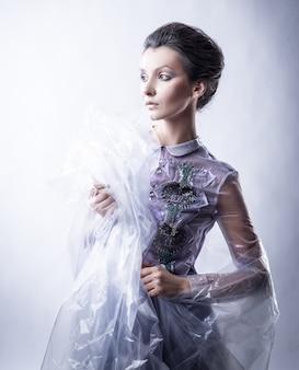 ファッショナブルなドレスと透明なケープの美しい若い女性
