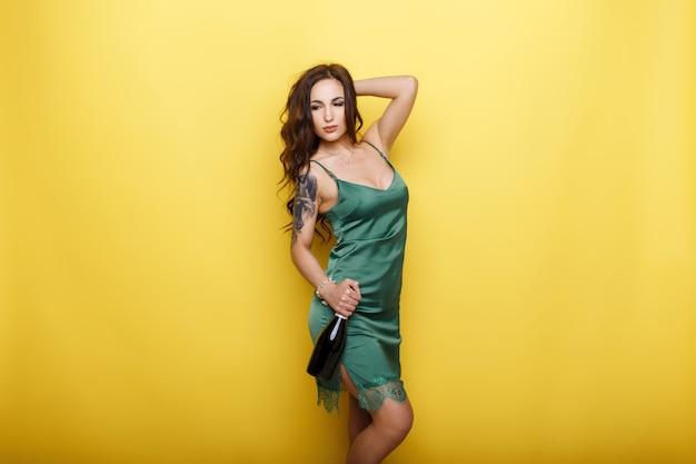 노란색 벽 근처 포즈 병 유행 이브닝 드레스에 아름 다운 젊은 여자