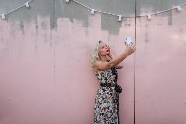 유행 빈티지 드레스에 아름 다운 젊은 여자는 분홍색 벽 근처 거리에 전화로 사진을 걸립니다