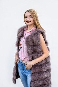 白い壁に毛皮のコートを着た美しい若い女性。美容とファッション。
