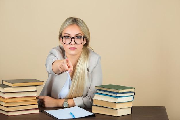 眼鏡とスーツの美しい若い女性は本とテーブルに座っています