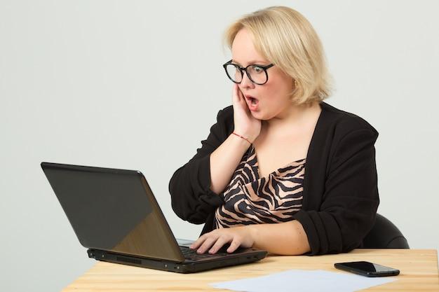 Красивая молодая женщина в очках за столом с ноутбуком