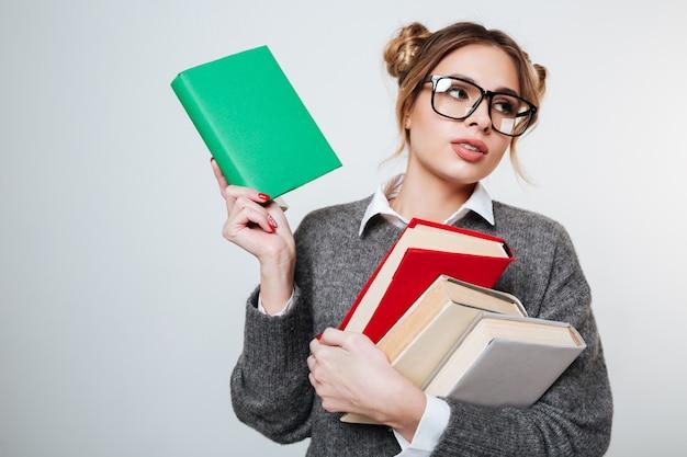 Красивая молодая женщина в очках, холдинг красочные книги