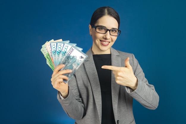 Красивая молодая женщина в очках держит в руках много тенге.