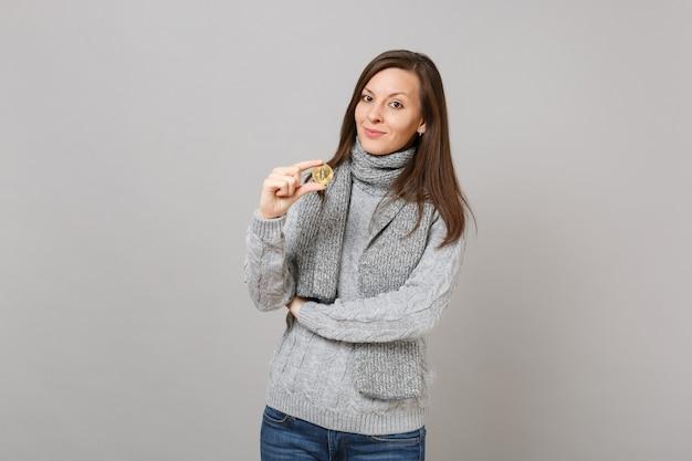 회색 스웨터를 입은 아름다운 젊은 여성, 스카프는 회색 벽 배경에 격리된 비트코인 미래 통화를 보유하고 있습니다. 건강한 패션 라이프스타일, 사람들의 진심 어린 감정, 추운 계절 개념. 복사 공간을 비웃습니다.