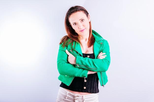 Красивая молодая женщина в зеленой куртке со скрещенными руками. концепция закрытия