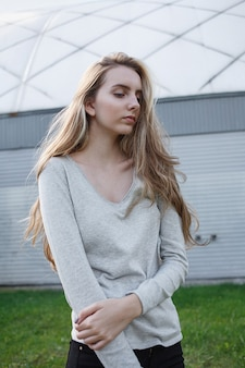 灰色のブラウス、黒のジーンズ、建物の前の地面にポーズをとってかわいいモデルの屋外の肖像画の美しい若い女性