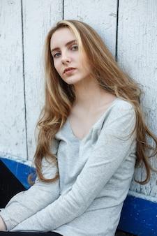灰色のブラウス、壁や柵でポーズをとってかわいい魅力的なモデルの屋外の肖像画の美しい若い女性