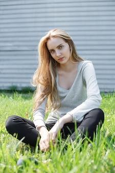 灰色のブラウス、壁で地面にポーズをとってかわいいモデルの屋外の肖像画の美しい若い女性