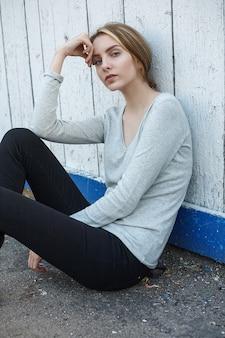灰色のブラウス、壁や柵でポーズをとってかわいい思慮深いモデルの屋外の肖像画の美しい若い女性