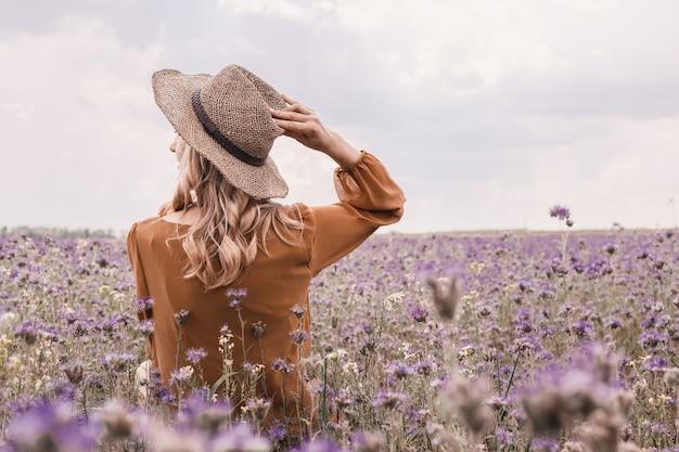 Красивая молодая женщина в шляпе в сиреневом поле. цветущие цветы
