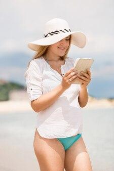 ビーチでデジタル タブレットに取り組んでいる帽子の美しい若い女性