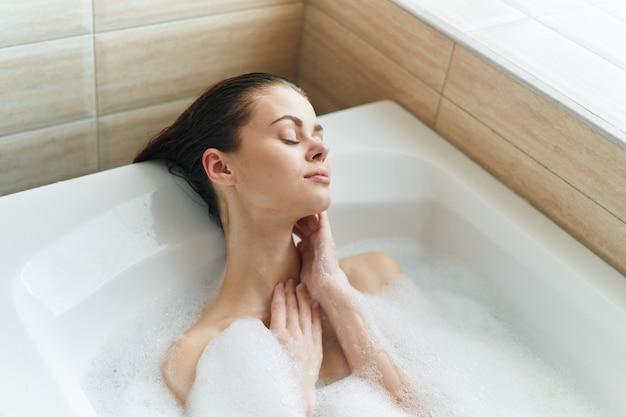 彼女の美しい雪のように白いバスタブで美しい若い女性が休んで、リラックス、泡とバスタブ