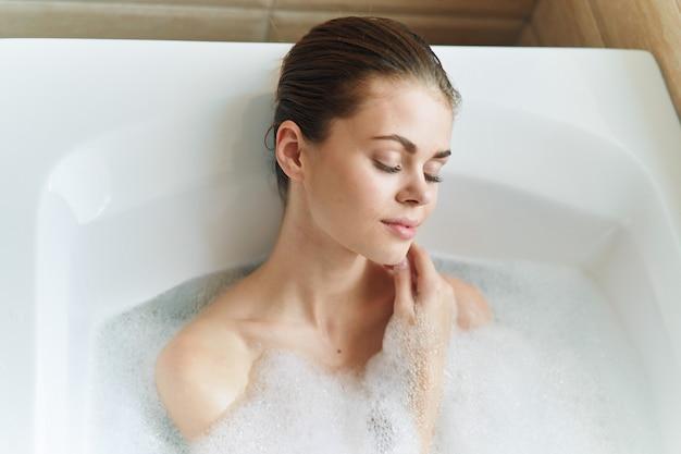 彼女の美しい真っ白な浴槽の美しい若い女性は休んでリラックスし、美しい証拠、泡付きの浴槽