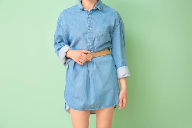 色の表面にジーンズの服を着た美しい若い女性