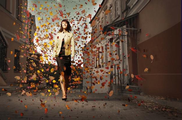 葉の間で秋の通りを歩いてレザージャケットの美しい若い女性