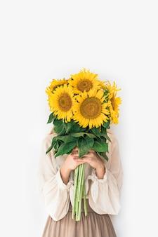 白い背景のヒマワリの花束を保持しているリネンのドレスで美しい若い女性。秋のコンセプトです。
