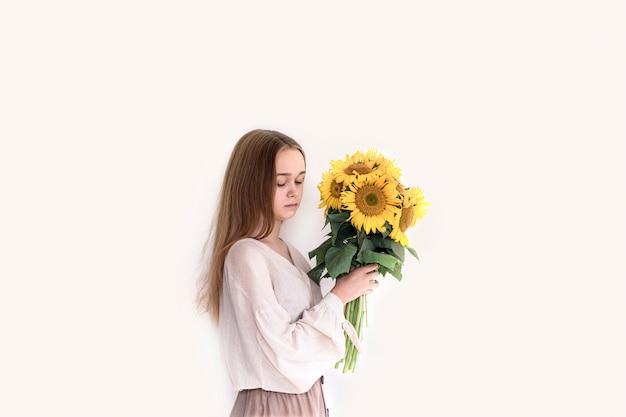 Красивая молодая женщина в льняном платье держит букет подсолнухов на белом