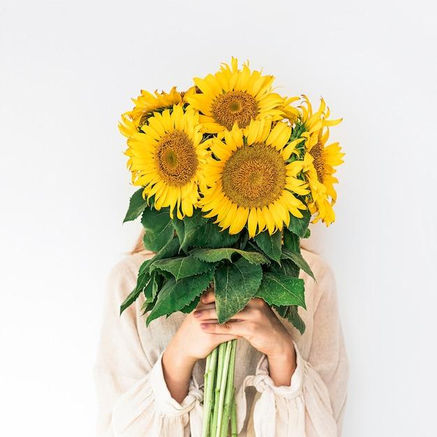 白にひまわりの花束を保持しているリネンのドレスの美しい若い女性