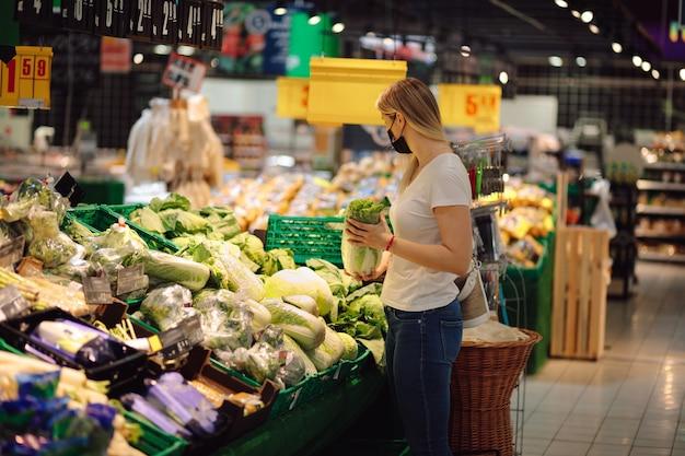마스크에 아름 다운 젊은 여자는 슈퍼마켓에서 야채와 허브를 선택합니다. 적절한 영양. 일상 생활. 자연 식품. 식품. 개인 보호 장비. 전염병의 사회 생활.