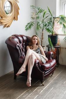 雑多なドレスを着た美しい若い女性、素足でかわいいモデルの屋内の肖像画。居心地の良い部屋で肘掛け椅子に座っています。自宅でポーズをとる自然なきれいな女性