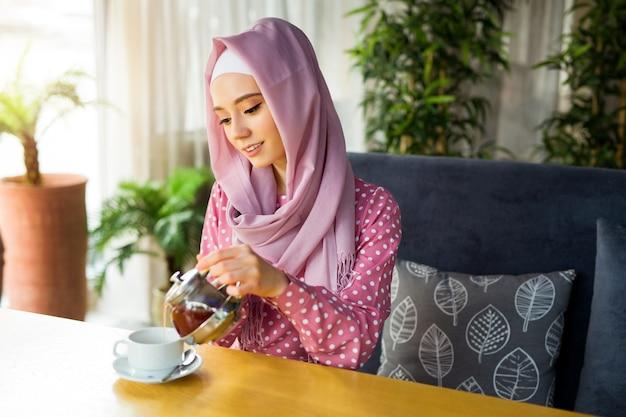 Красивая молодая женщина в мусульманском платье пьет чай в ресторане