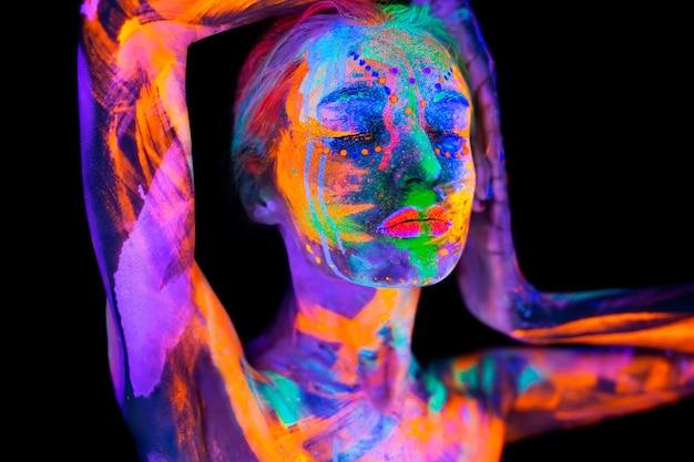 ネオンの光の中の美しい若い女性。カラフルなメイクで uv ライトでポーズをとる蛍光メイクのモデルのポートレート