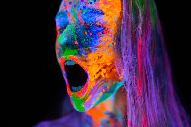 ネオンの光の中の美しい若い女性。 uv ライトと悲鳴の中でポーズをとる蛍光メイクのモデルの肖像画