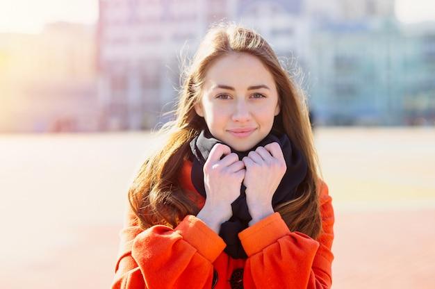 Красивая молодая женщина в оранжевом пальто гуляя в город