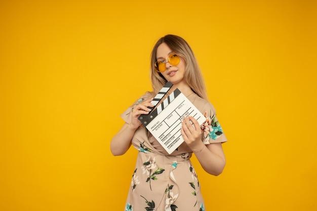 Красивая молодая женщина в оранжевых очках, холдинг классический белый фильм, делая с 'хлопушкой', изолированные на желтом фоне. люди искренние эмоции, концепция образа жизни. рекламная площадка