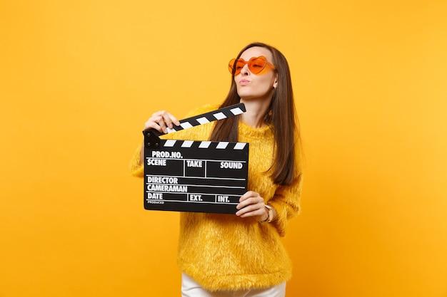 脇を見て、黄色の背景で隔離のカチンコを作る古典的な黒いフィルムを保持しているオレンジ色のハートの眼鏡の美しい若い女性。人々は誠実な感情、ライフスタイル。広告エリア。
