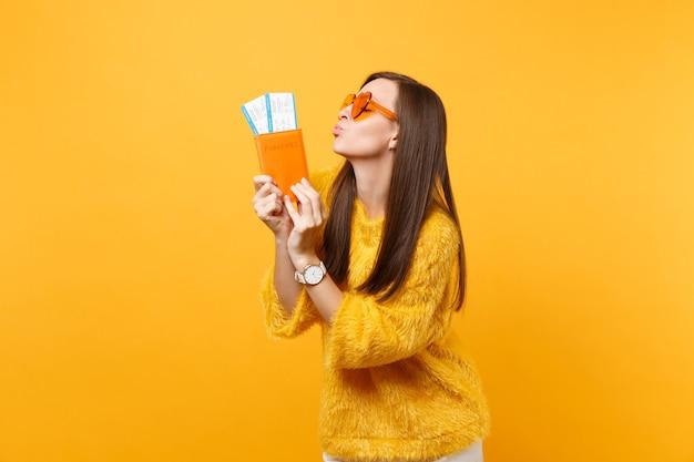 주황색 하트 안경을 쓴 아름다운 젊은 여성이 여권을 들고 공기 키스를 보내는 입술을 불고, 노란색 배경에 격리된 탑승권 티켓을 보냅니다. 사람들은 진실한 감정, 라이프 스타일. 광고 영역입니다.