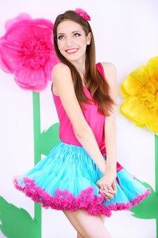 装飾的な表面のささいなスカートの美しい若い女性