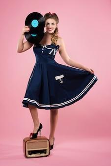ビニールを保持しているピンナップスタイルの服を着た美しい若い女性