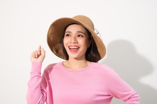 핑크 드레스와 태양 모자에 아름 다운 젊은 여자는 복사 공간에서 가리키는