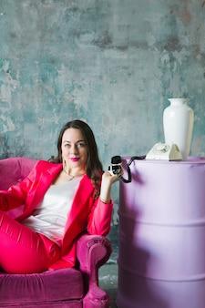 ロフトのインテリアに古い電話でピンクの椅子に座っているピンクのスーツで美しい若い女性