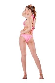 ピンクの水着姿の美しい若い女性