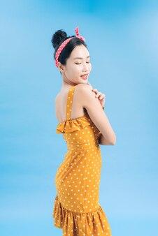 Красивая молодая женщина в платье в горошек стоит, смотрит в сторону и улыбается
