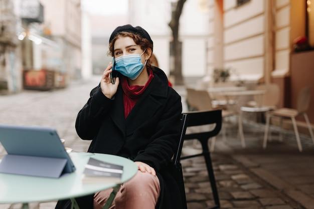 カフェテラスで屋外に座っている間携帯電話で話している保護マスクの美しい若い女性。感染症とパンデミックの時間の概念。
