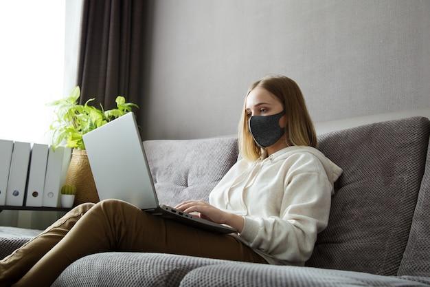 보호 의료 마스크에 아름 다운 젊은 여자는 집에서 원격 작업 또는 온라인 연구가 있습니다. 코로나 바이러스 코로나 19 봉쇄 기간 동안 소파에 아늑한 홈 오피스. 노트북을 사용하는 프리랜서 원격 작업.