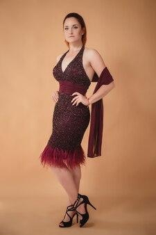 スタジオでポーズをとって紫色のドレスを着た美しい若い女性。イブニングイベントのクラシックメイク