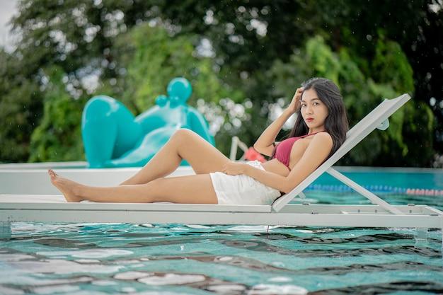 수영장 근처 해변 의자에 빨간 비키니 입은 아름다운 젊은 여자